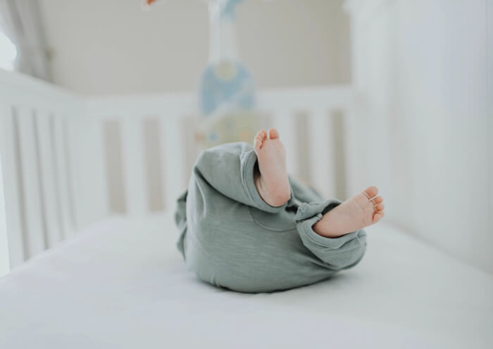 Baby sleeping on back in baby cot