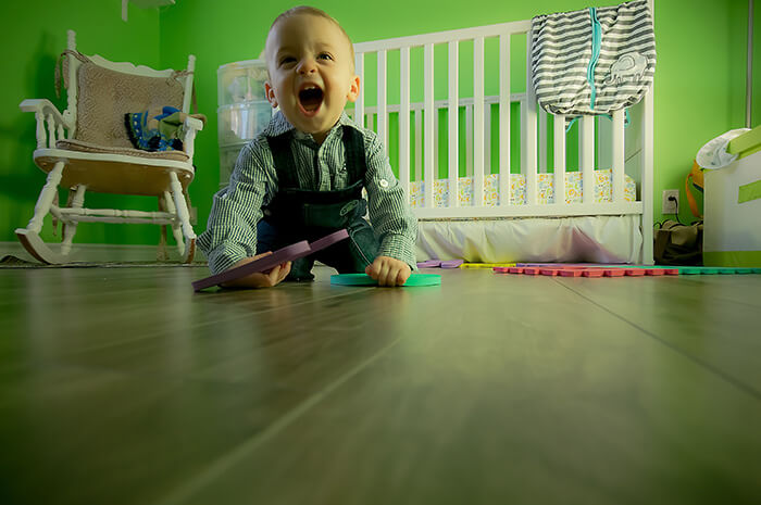 Toddler playing with toys in front of baby cot