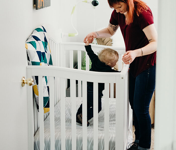 Mum lifting baby out of baby cot