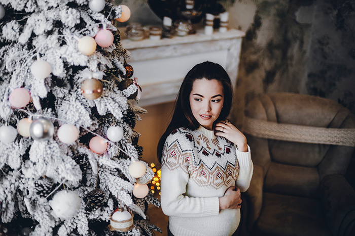 Pregnant lady in Christmas jumper standing by Christmas tree