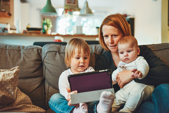 Mum, baby and toddler playing on a tablet