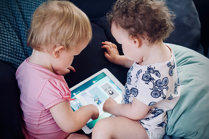 Two babies using a tablet