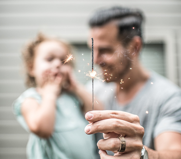 a dad and his daughter using a sparkler